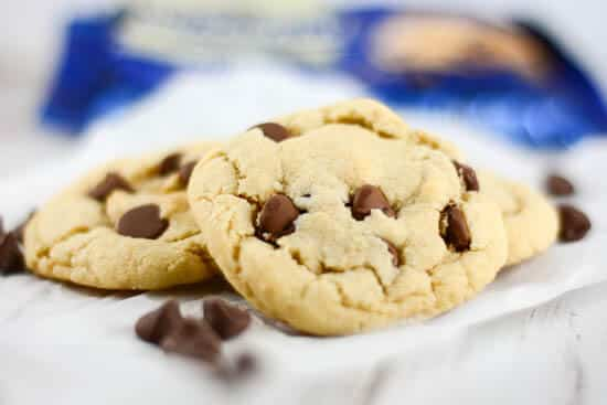 Chocolate chip cookies on white parchment paper with blue chocolate chip package in background.