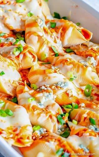 Closeup of Buffalo Chicken Stuffed Shells in casserole dish.