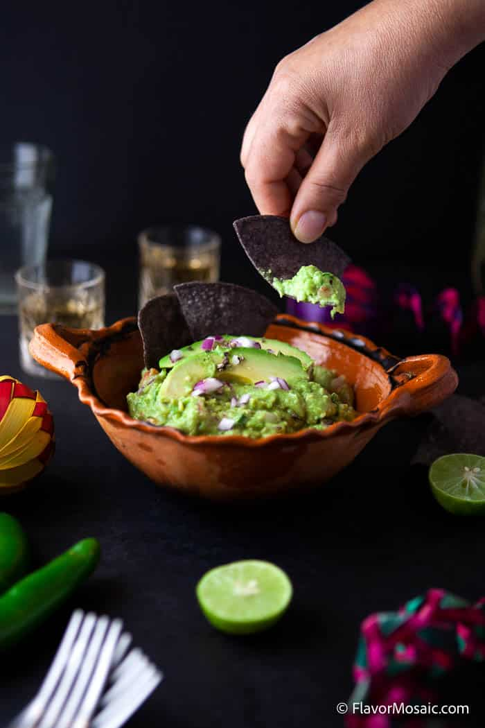 Orange bowl of guacamole with a black background with a hand holding a tortilla chip with guacamole on it. Slimed limes forks and shot glasses surround the guacamole.