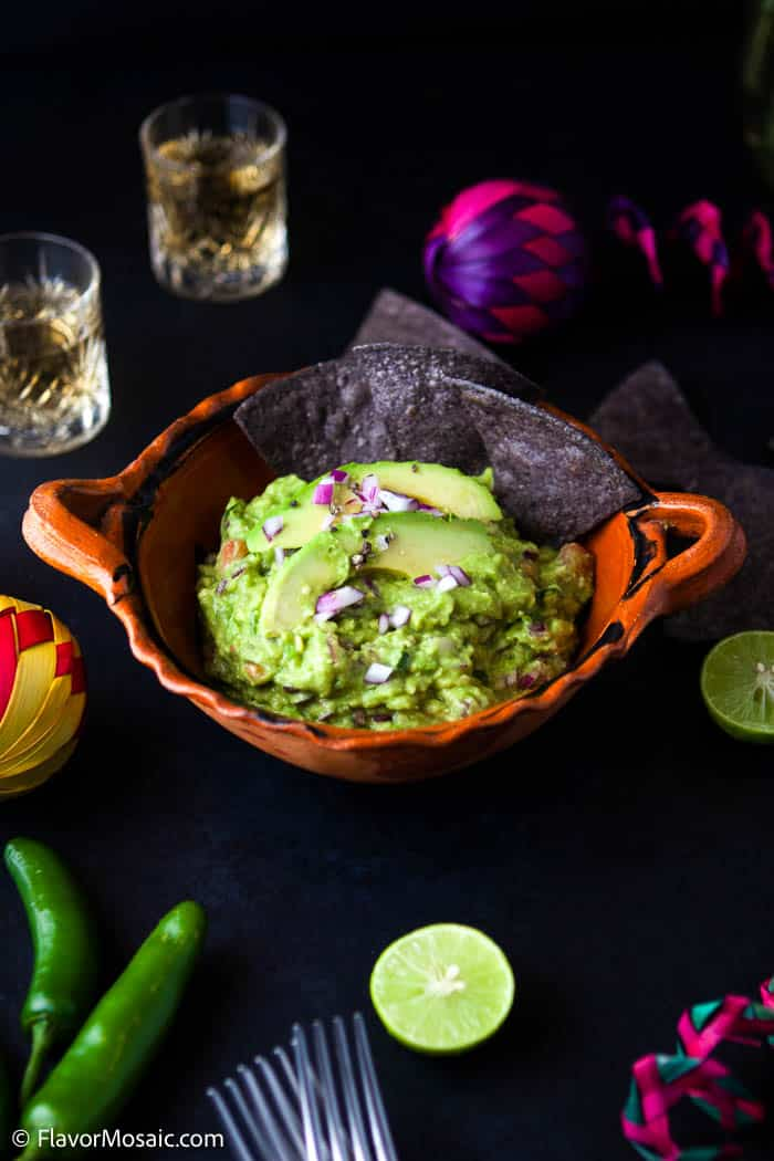 orange bowl with guacamole with dark tortilla chips with a black background surrounded by shot glasses, lime slices, chilies and a pink and purple decoration.