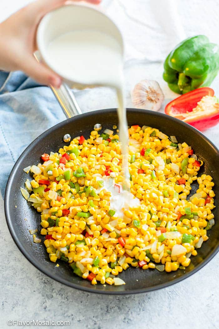 Pouring cream into a skillet of Maque Choux corn.