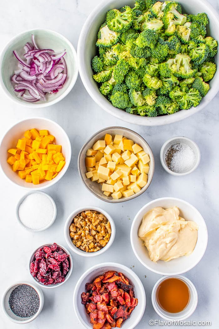 Overhead view of individual bowls with ingredients for Broccoli Salad on white marble background.