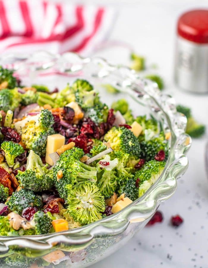 Photo of glass bowl with broccoli salad with cranberries, bacon and cheddar cheese on white marble countertop