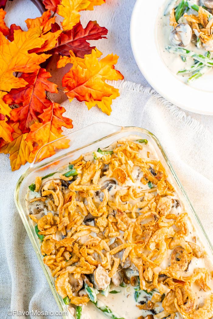 Overhead view of cooked green bean casserole with one spoonful removed and a white plate with a partial view of a single serving in the upper right corner with fall leaves as decoration in the upper left corner.