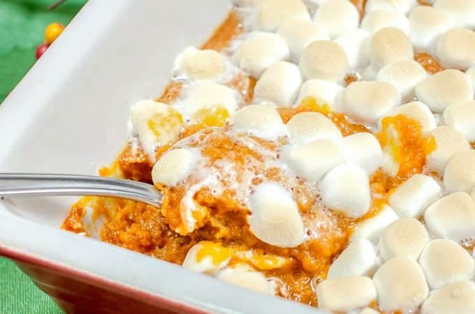 Sweet Potato Casserole with Marshmallows with a spoon lifting sweet potatoes out of casserole dish
