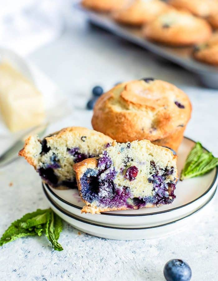 plate with 2 blueberry muffins - one sliced in half with muffin tin pan in the background.