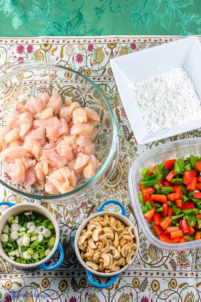 Overhead photo of ingredients for Easy Spicy Chinese Cashew Chicken, including raw chicken cubes, cornstarch, red and green bell peppers, green onions, and cashews.