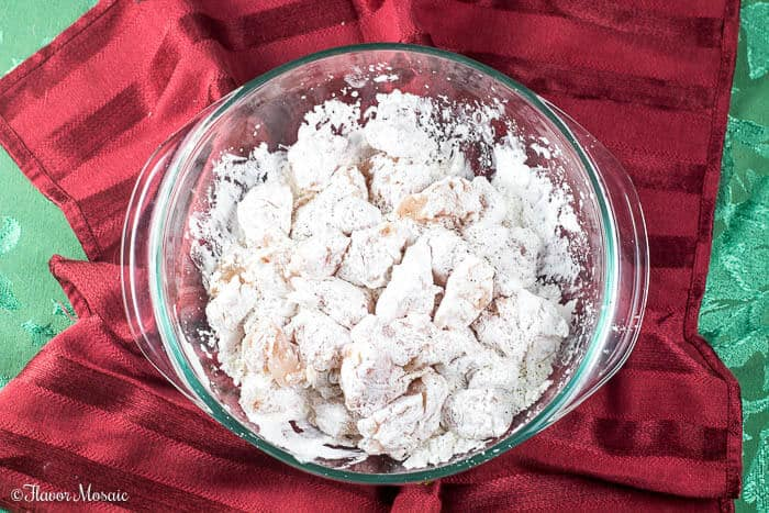Overhead photo of chicken cubes in a bowl covered in cornstarch in preparation for Easy Spicy Chinese Cashew Chicken recipe