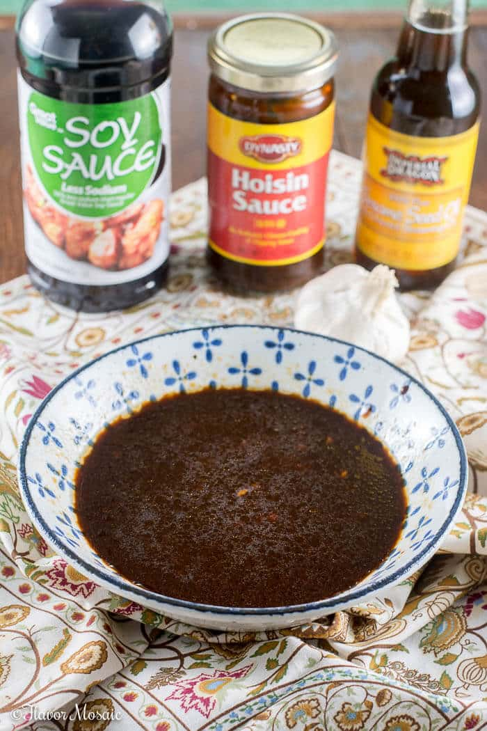 Photo of sauce in a bowl with jars of soy sauce, hoisin sauce, and sesame oil in the background. This is the sauce for Easy Spicy Chinese Cashew Chicken
