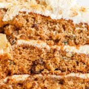 Close up of the side of a slice of 3-layer frosted carrot cake.
