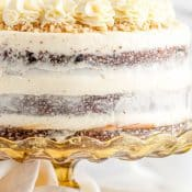1 photo pin with a side view of a whole decorated carrot cake sitting on an elevated cake stand..