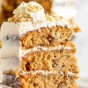 Side view of 3-layer frosted carrot cake with a partial blurred view of the rest of the cake in the background.