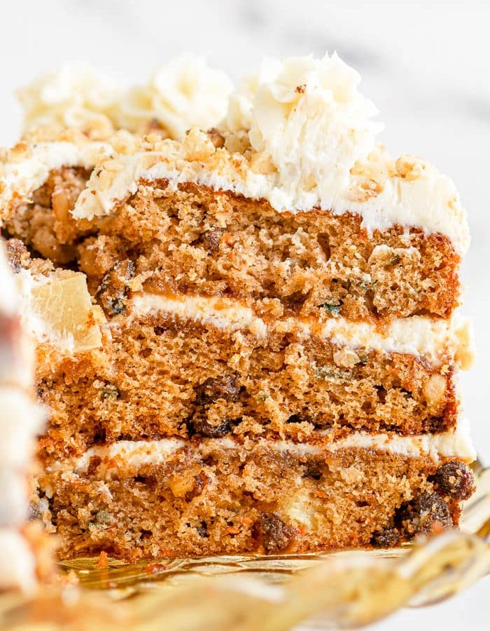 Close up view of the side of a slice of 3-layer homemade carrot cake with cream cheese frosting, and white marble background.