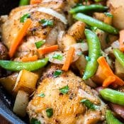 Chicken Vesuvio - an Italian-American chicken dinner in a skillet with potatoes, garlic, snap peas and carrots. It is popular in Chicago.