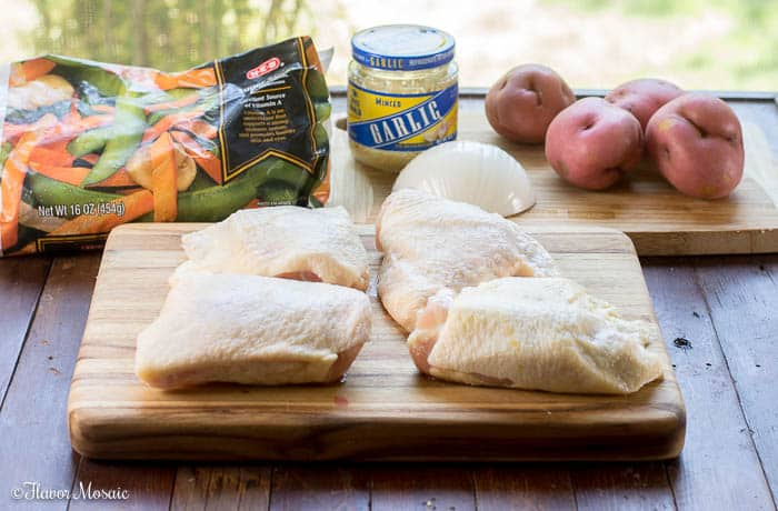 Ingredients for Chicken Vesuvio - an Italian-American chicken dinner in a skillet with potatoes, garlic, snap peas and carrots. It is popular in Chicago.