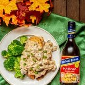 Stuffed Chicken Marsala - overhead photo of dinner plate with Stuffed Chicken Marsala with Marsala sauce and a side of broccoli.
