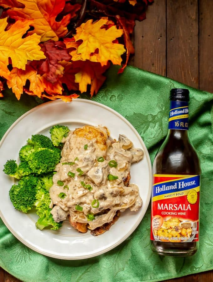 Stuffed Chicken Marsala - overhead photo of dinner plate with Stuffed Chicken Marsala with Marsala sauce and a side of broccoli.