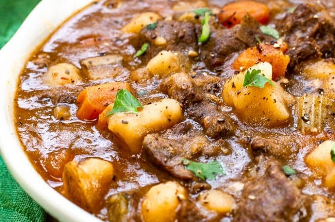 Big white bowl of a thick beef stew with potatoes, carrots, celery and chopped parsley.