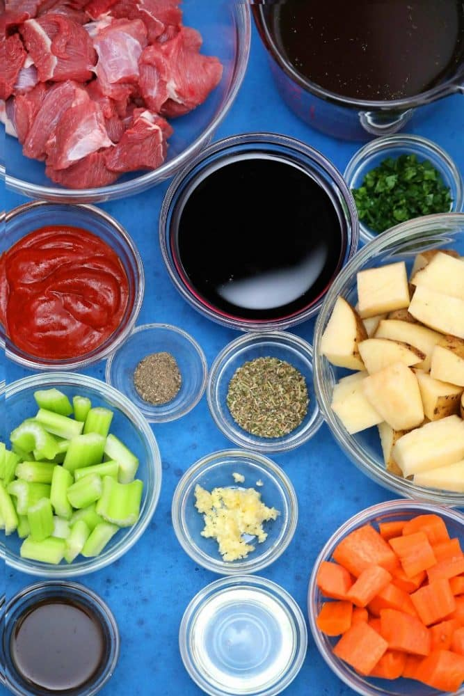 Overhead view of Ingredients for Instant Pot Beef Stew in small glass bowls with blue background by Flavor Mosaic