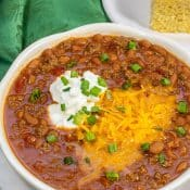 Big white bowl of Instant Pot Chili with shredded cheese green onions and sour cream.