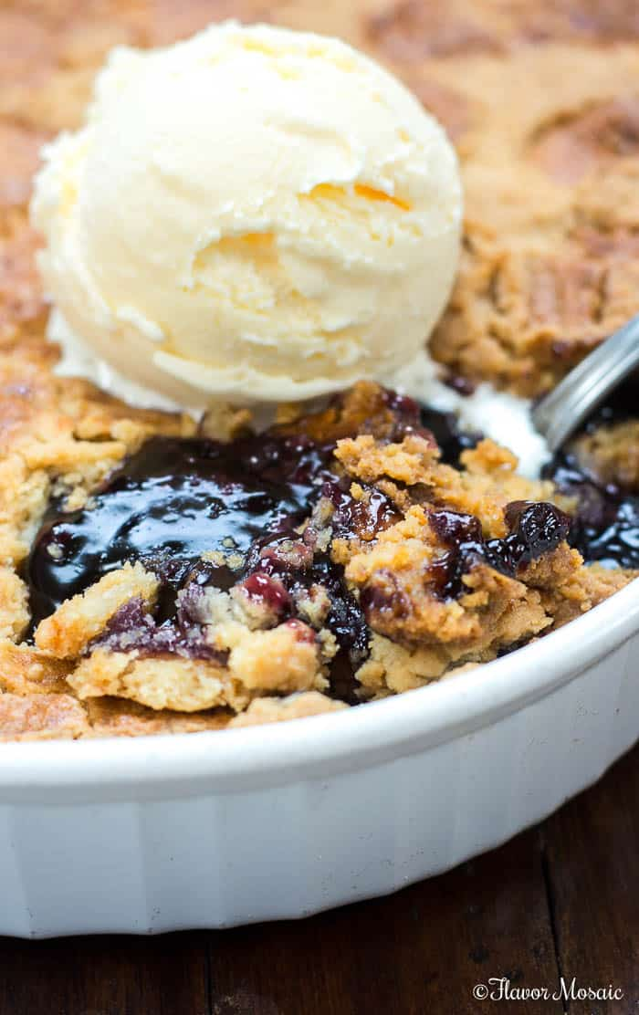 Photo of Blueberry Dump Cake in cake pan with a corner of the blueberry dump cake spooned out and the crust topped with ice cream.