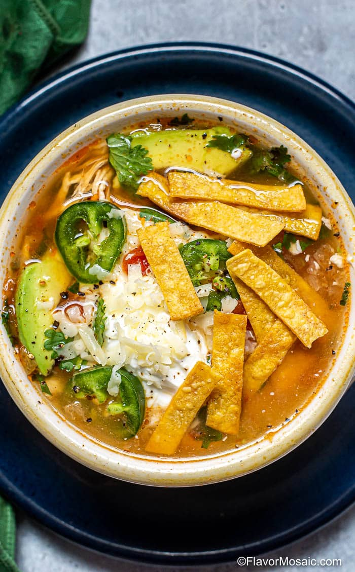 Overhead photo of a white bowl of Chicken tortilla Soup topped with tortilla strips, sliced jalapeños, and cilantro, sitting on a blue plate.