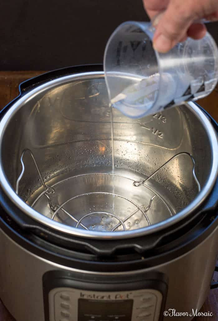 Pouring water into an Instant Pot, which is the first step in making Instant Pot Hard Boiled Eggs.