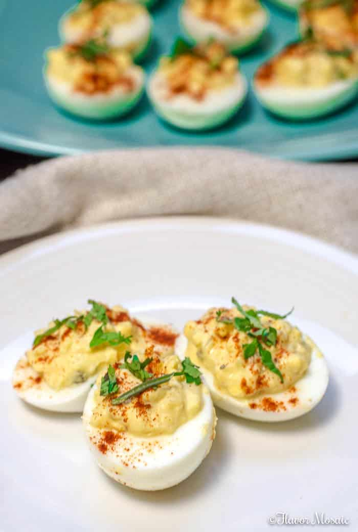3 Southern Deviled Eggs on a white plate with a blue platter of deviled eggs in the background.