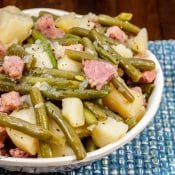 Photo of Instant Pot Ham Green Beans and Potatoes in white bowl on blue placemat on brown wood table.
