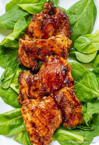 A white platter with Sweet Tea BBQ Chicken Thighs sitting on top of spinach leaves on platter.