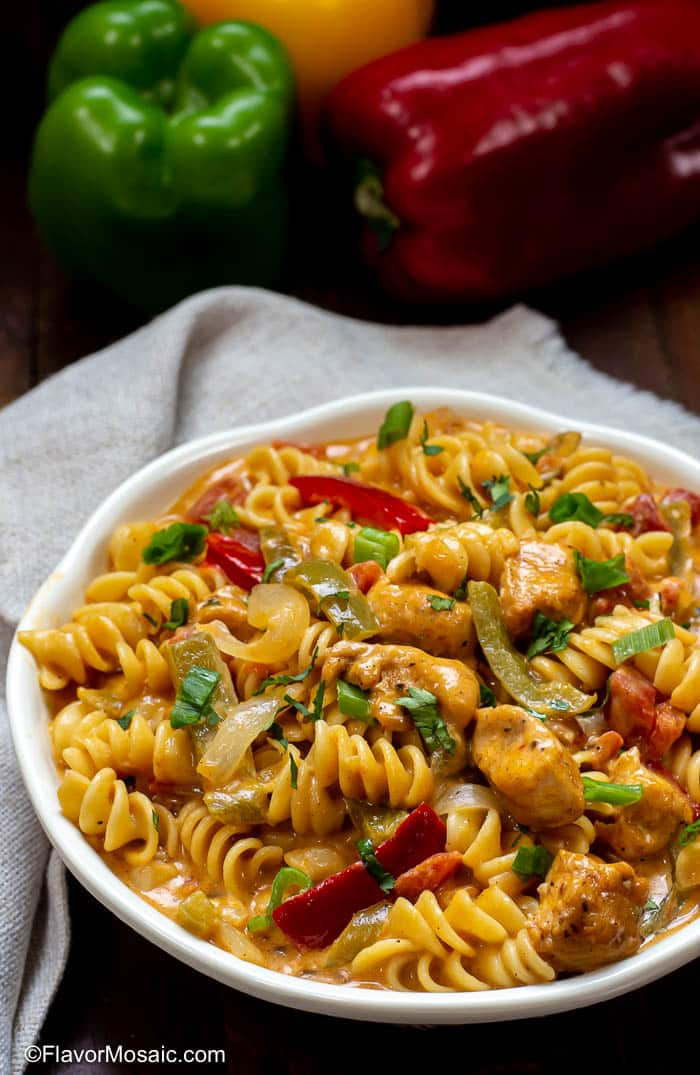 White bowl with Chicken Fajita Pasta with sliced red and green bell peppers on a dark wood table with a gray napkin and red, yellow and green bell peppers in the background.
