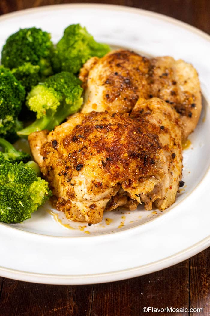 2 pieces Instant Pot Chicken Thighs and a side of broccoli on white plate on dark wood table.