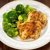 Two pieces of Instant Pot Chicken Thighs with broccoli on a white plate and dark wood table.