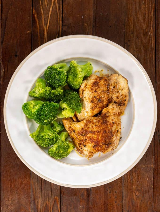 Overhead view of 2 pieces of Instant Pot Chicken Thighs and Broccoli on white plate stilton on dark wood table.