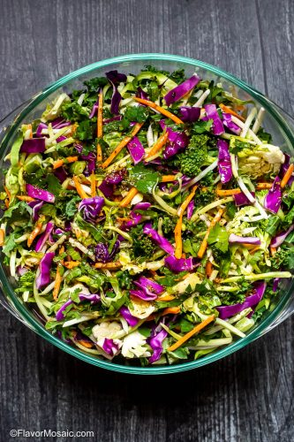 Glass bowl of Mexican Cabbage Slaw with Red Cabbage and carrots sitting on top of old gray barn wood table.