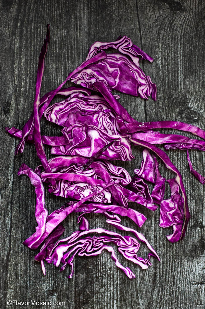 Red Cabbage for Mexican Cabbage Slaw sitting on top of dark gray wood table.