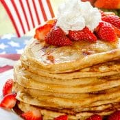Stack of Strawberry Pancakes topped with strawberries, maple syrup, and whipped cream, on white plate with bowl of strawberries in the background.