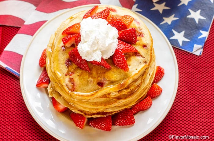 overhead shot of stack of strawberry pancakes on white plate with red, white and blue napkins.