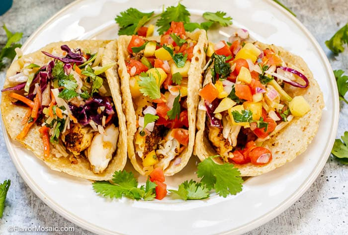 Horizontal photo of 3 Blackened Fish Tacos on white plate garnished with cilantro