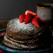 Vertical photo of a stick of Chocolate Chip Chocolate Pancakes topped with strawberries on a blue plate.