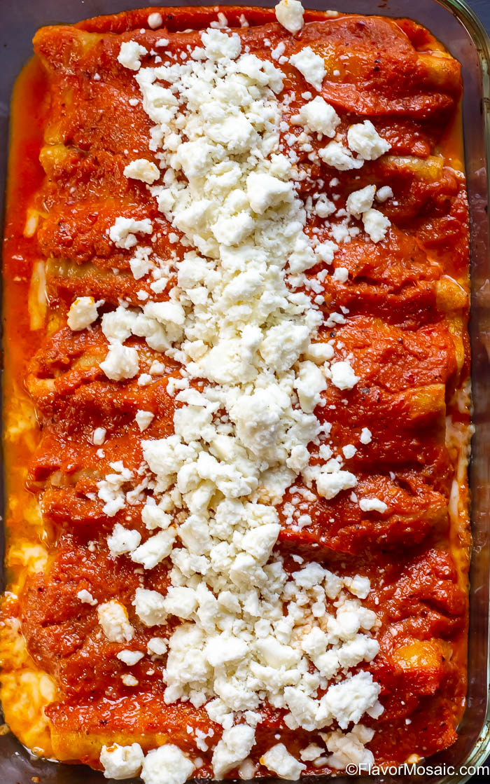 overhead photo of vertical casserole dish with Enchiladas Rojas de queso topped with queso fresco.