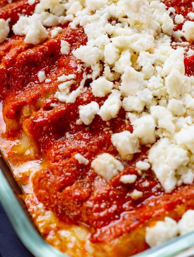 Overhead photo at an angle of a casserole dish of Enchiladas Rojas de queso topped with queso fresco.