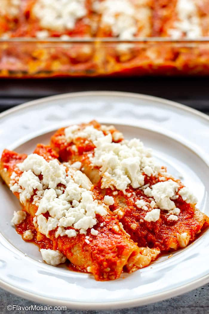 Two Enchiladas Rojas on a white plate topped with Queso fresco and a casserole dish of enchiladas in the background