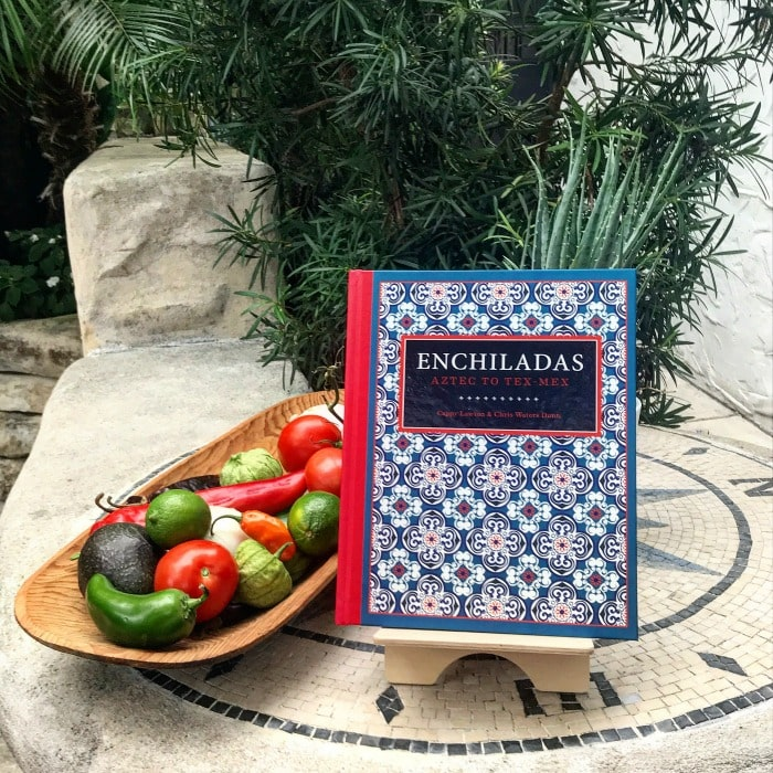 Photo of Enchiladas Cookbook sitting next to platter of peppers.