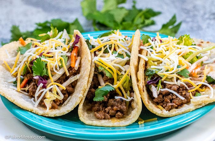 Horizontal photo shot from the side showing 3 ground beef tacos on a blue plate.