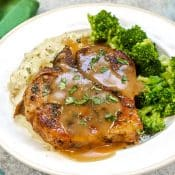 Vertical photo of Instant Smothered Pork Chops sitting on white plate with sides of broccoli and mashed potatoes.