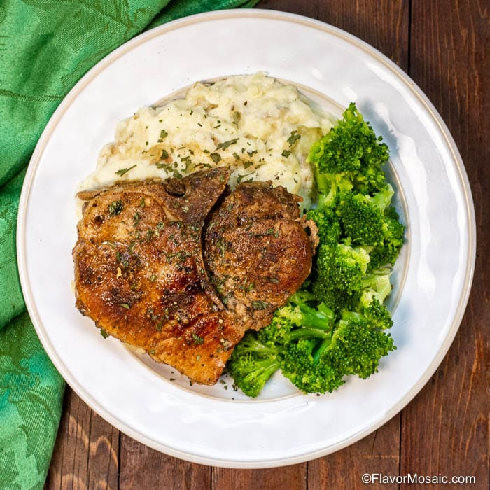 Overhead photo of Instant Pot Smothered Pork Chops (without gravy) sitting on a white dinner plate with broccoli and mashed potatoes.