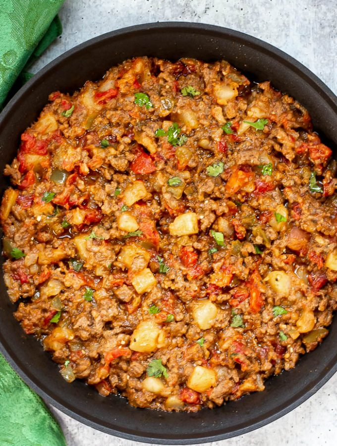 Vertical Overhead photo of Picadillo Con Papas (Tex-Mex style) in a black skillet on gray table with green napkin on the left side of the skillet.
