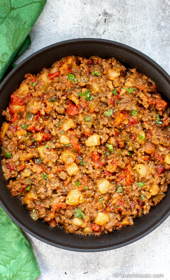 Vertical Overhead photo of Picadillo (Tex-Mex style) in a black skillet on gray table with green napkin on the left side of the skillet.