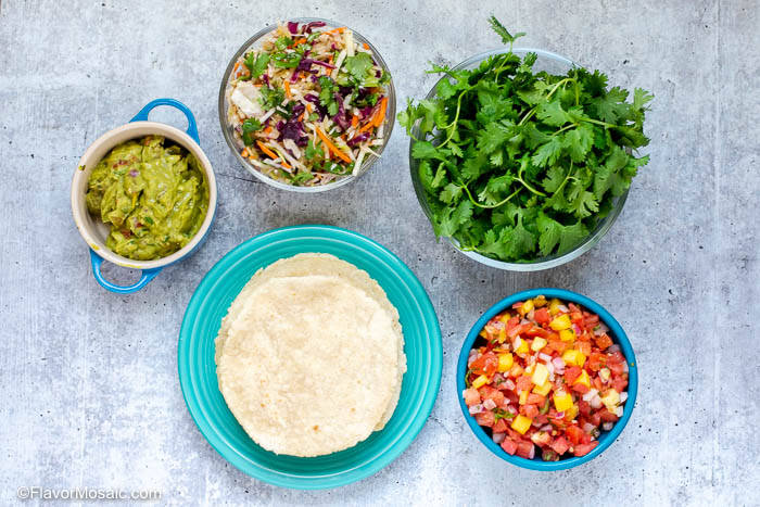 Overhead photo of taco toppings in separate bowls and corn tortillas on a plate.